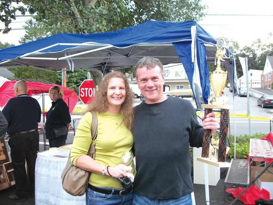 Photo by Lynn Fredricksen Diane Plunske and Arnie Schloemann celebrate Schloemann's first prize win for his homemade Cabernet Sauvignon at the Rotary Club's annual Day of Wine & Roses fundraising event at Forget Me Not Florist. Schloemann, who makes wine as a hobby, is a newcomer to the competition yet took top honors.