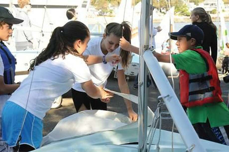 Submitted Photo Chris Izzo, right, is a Hamden resident. From left, seventh-grader Caroline Quinn, sophomore Marilee Bodden and seventh-grader Chris Izzo rig their sailing vessel.