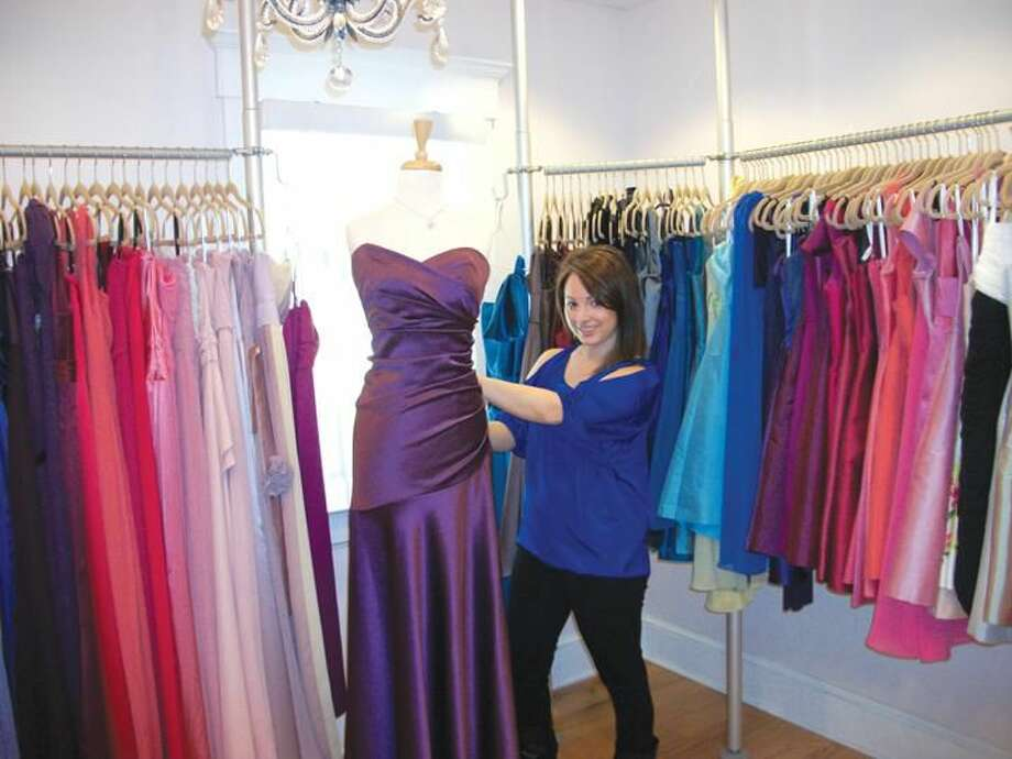 Photo by Lynn Fredricksen Lisa DeLeo adjusts a display gown at her boutique Simply Couture. The shop, at 30 State Street, offers a variety of dresses for proms, brides, and other occasions.