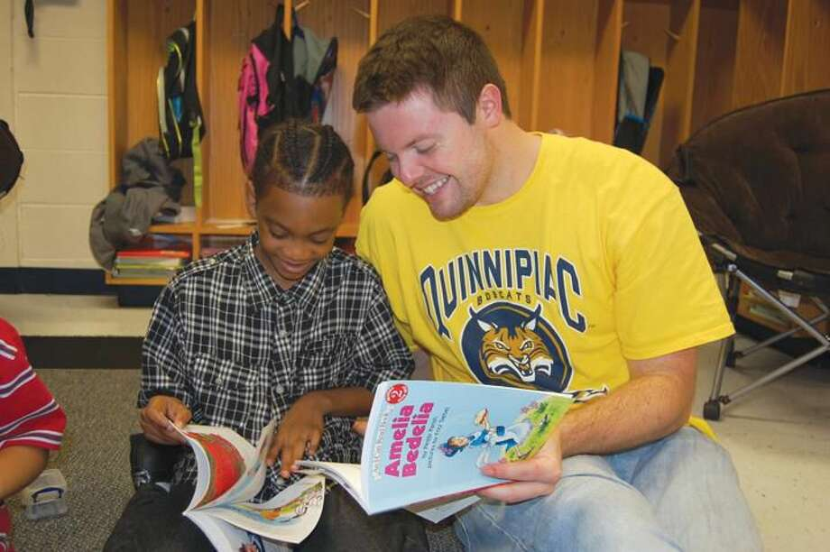 Submitted Photo Chris Nugent, right, a physician assistant student in the School of Health Sciences at Quinnipiac University, read to Jason Jackson, a student at ACES Mill Road School in North Haven, during the Big Read and Fitness Fair held Oct. 5 at the school.