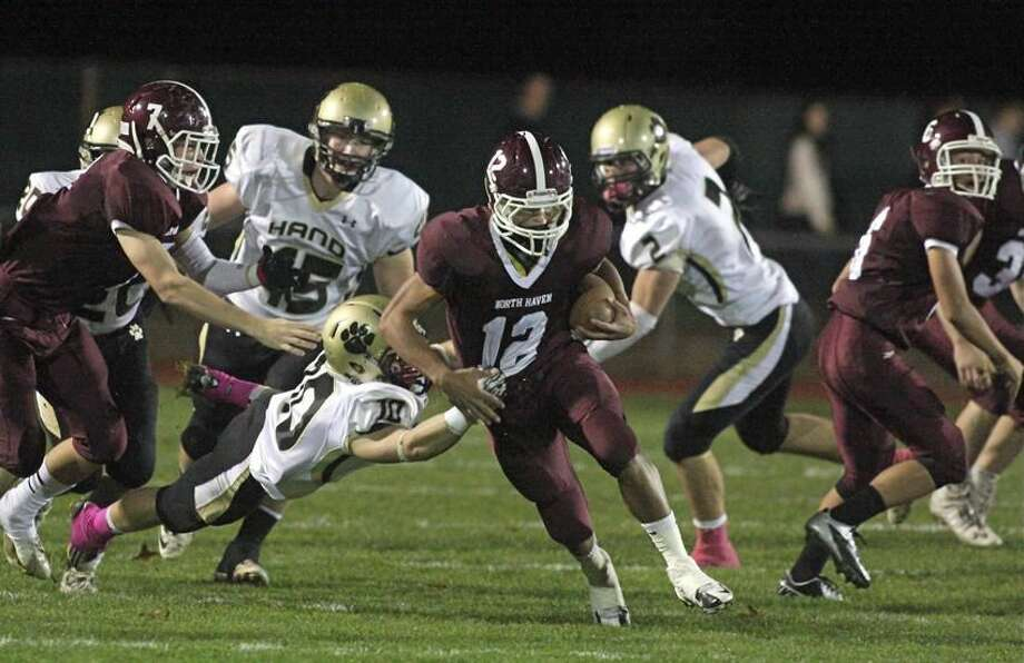 Photo by Russ McCreven North Haven's Quincy Pecora tries to break loose from Hunter Mayhew's grasp.