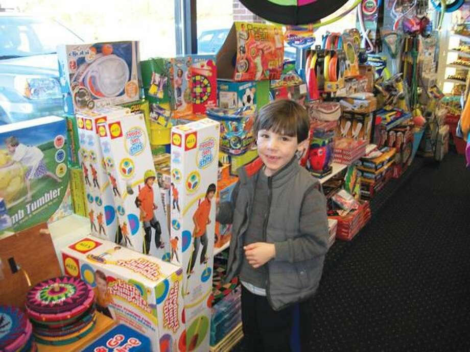 Photo by Lynn Fredricksen Aidan Nolan, 6, of Hamden, checks out a pogo stick at Evan's Toys on Whitney Avenue as part of Small Business Saturday.