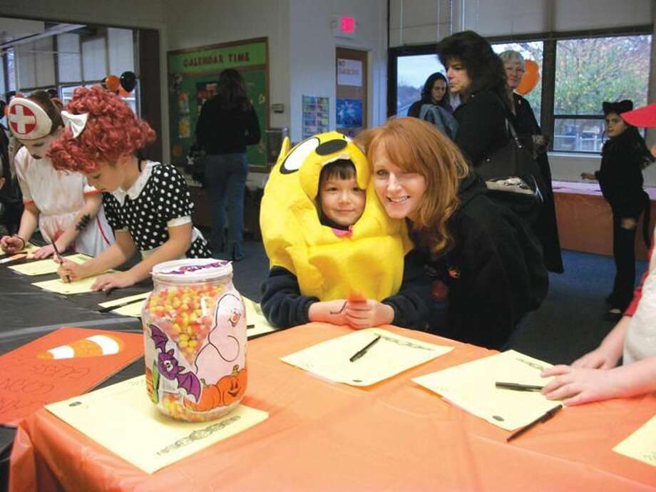 Photo by Lynn Fredricksen Above: Daniel Mahan (dressed as Jake from Adventure Time) and his Mom, Kelly Mahan, take a guess at how many candy corns are in the jar at the North Haven Community Services Halloween party last week.