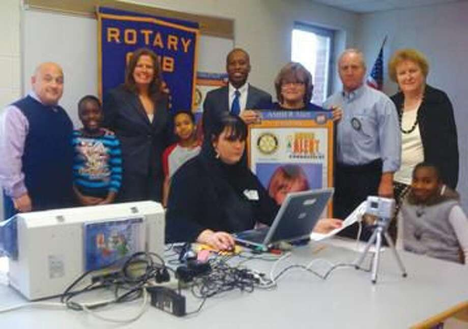 Submitted Photo Pictured with several Church Street School students are, left to right, Church Street School Principal Howard Henreich, Naugatuck Savings Bank Branch Manager and Rotarian Lisa Brewster, Mayor Scott Jackson, Town Representative and Rotarian Betty Wetmore, Rotarian Rit Azklar, Hamden Rotary Cub President Joena Russell (sitting), and Superintendent of Schools Fran Rabinowitz.