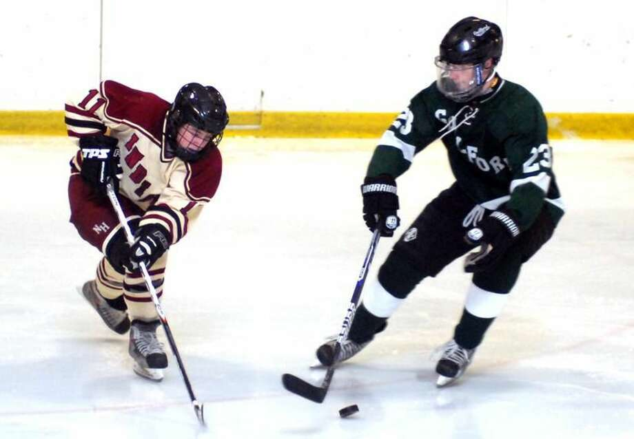 Photo by Dave Phillips North Haven's John Jensen battles Guilford's Zach Cattaruzza for control of the puck during Saturday night's 5-2 victory at the Northford Ice Pavilion.