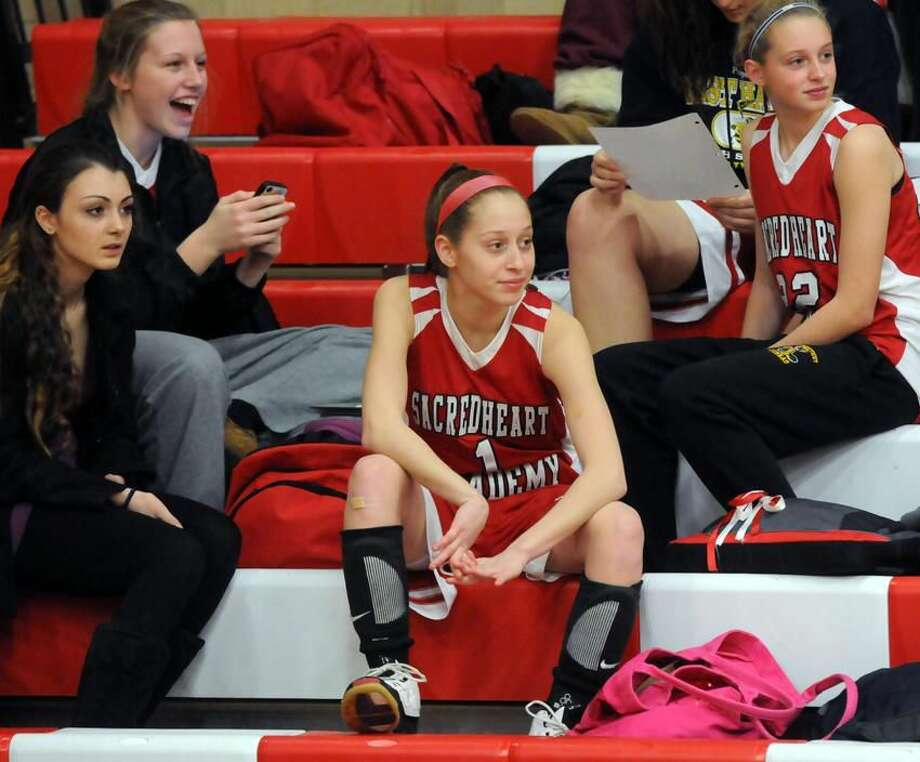 Sacred Heart basketball players Shyla Osmond watches her teammates warm up before a recent game. Osmond, who lost her memory after suffering a head injury, is fully recovered and playing basketball again. (Mara Lavitt/New Haven Register) 12/13/12