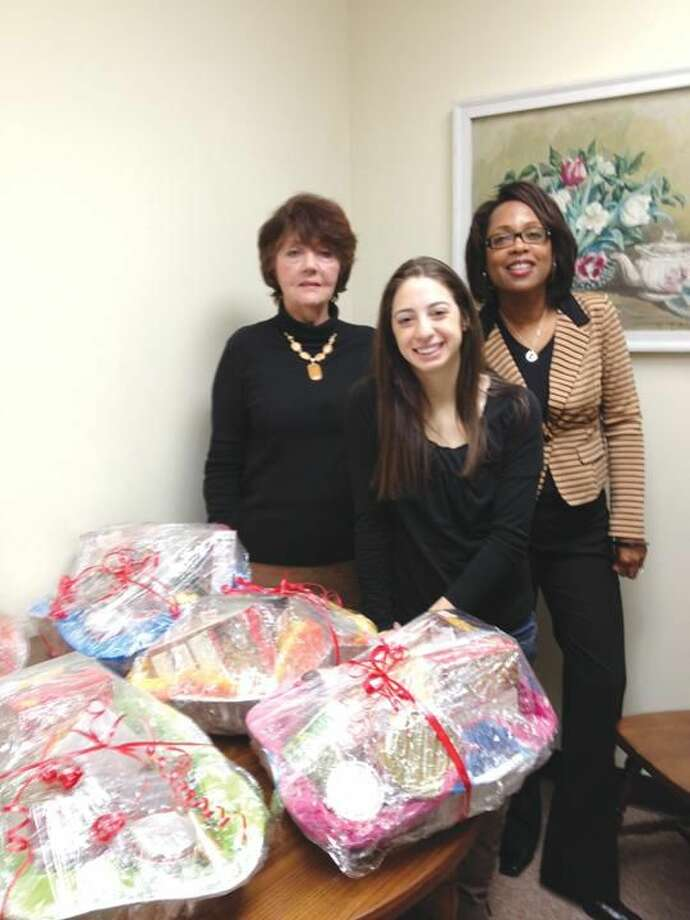 Submitted photo by Donna Diaz Quinnipiac University School of Nursing student Emily Schiarizzi, center, presents the Quinnipiac Student Nurses Association's Thanksgiving food basket contributions to Florence Klemenz, left, and Cherylann Savo, resident service coordinators at the senior housing facility, just before Thanksgiving.