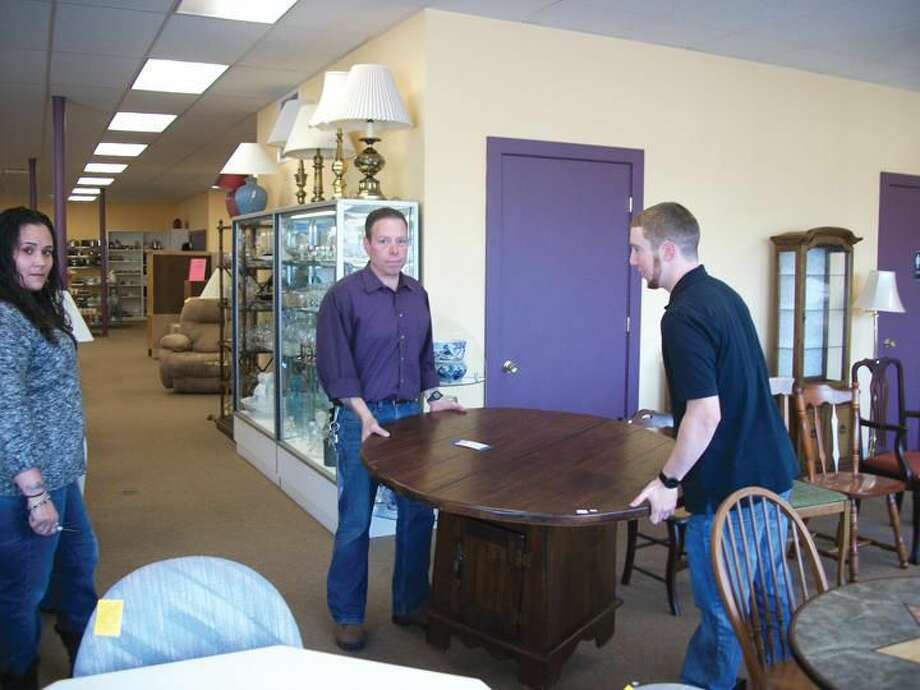 William Soucie (center) and Nate Klein (right) move a table out of the showroom at Helping Hands Community Thrift Store and Furniture Bank, 77 State Street in North Haven, as store manager, Angie Soto looks on. The store provides members of the community with an opportunity to direct their donation to the non-profit organization of their choice. There is also a furniture bank where qualifying individuals can choose household furnishings at no cost.