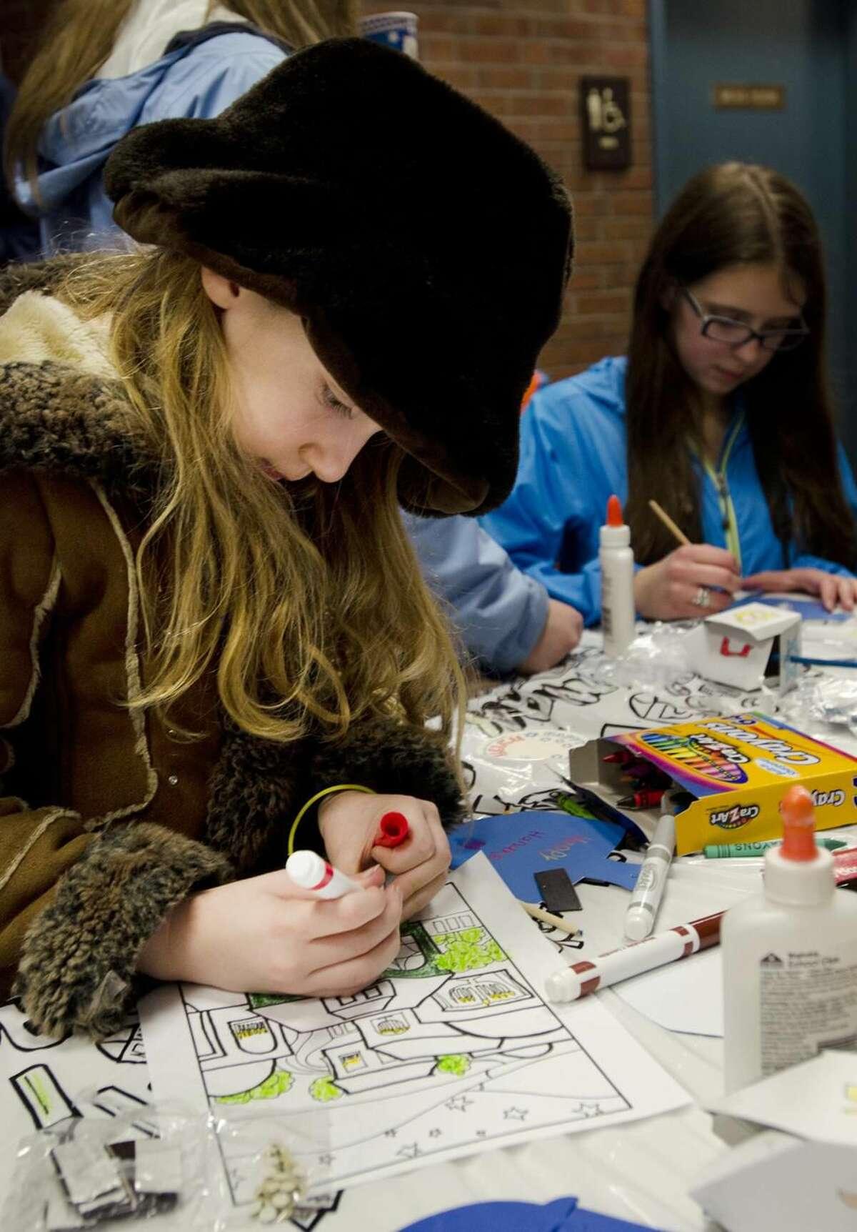 Hamden-Stephanie Caplan,9, of Cheshire, does some coloring during Chanukah festivities at Thorton Wilder Hall. Melanie Stengel/Register