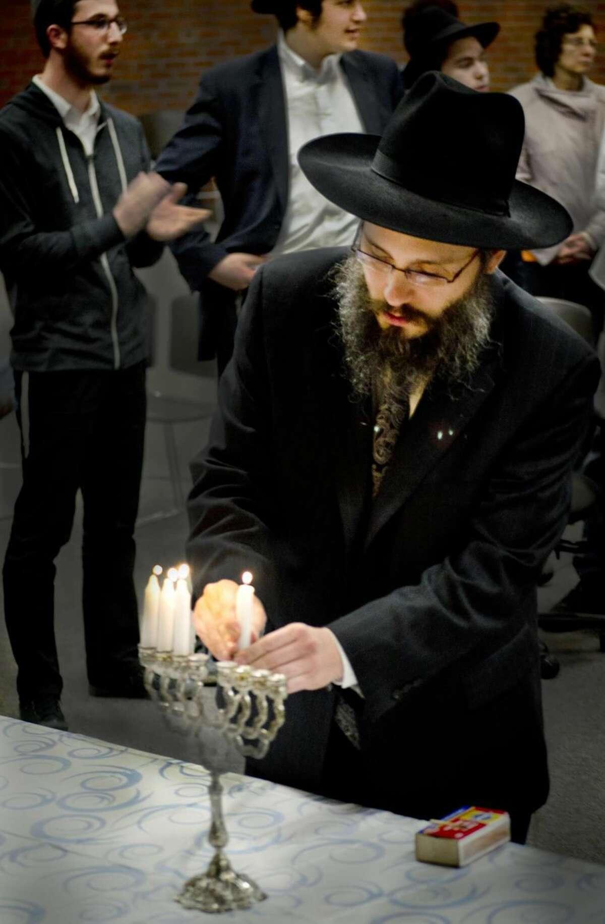 Hamden- Rabbi Menachem Pierkarski, of Chabad Hamden, places the Shamash into the Menorah after a Chanukah Menorah lighting ceremony at Thorton Wilder Hall. Melanie Stengel/Register