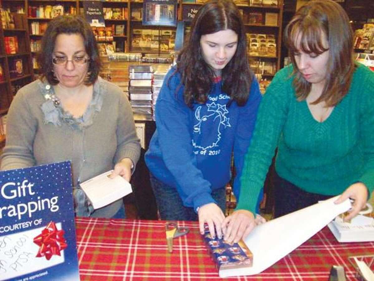 Submitted Photo Shown are HHS PTSA member Gina Harrison, SADD member Jillian Zaleski, and Joanne Courtemanche of HHS PTSA as the wrap gifts at Barnes and Noble during the Holiday Season.