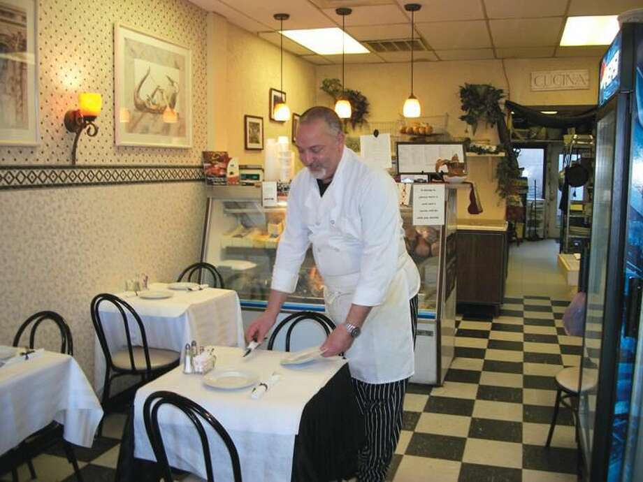 Photo by Lynn Fredricksen Pasquale Puglia Jr., aka The Everyday Gourmet, sets a table at his 3000 Whitney Ave. eatery. In business for 29 years, The Everyday Gourmet is a full service catering establishment that also features an 18-seat restaurant.
