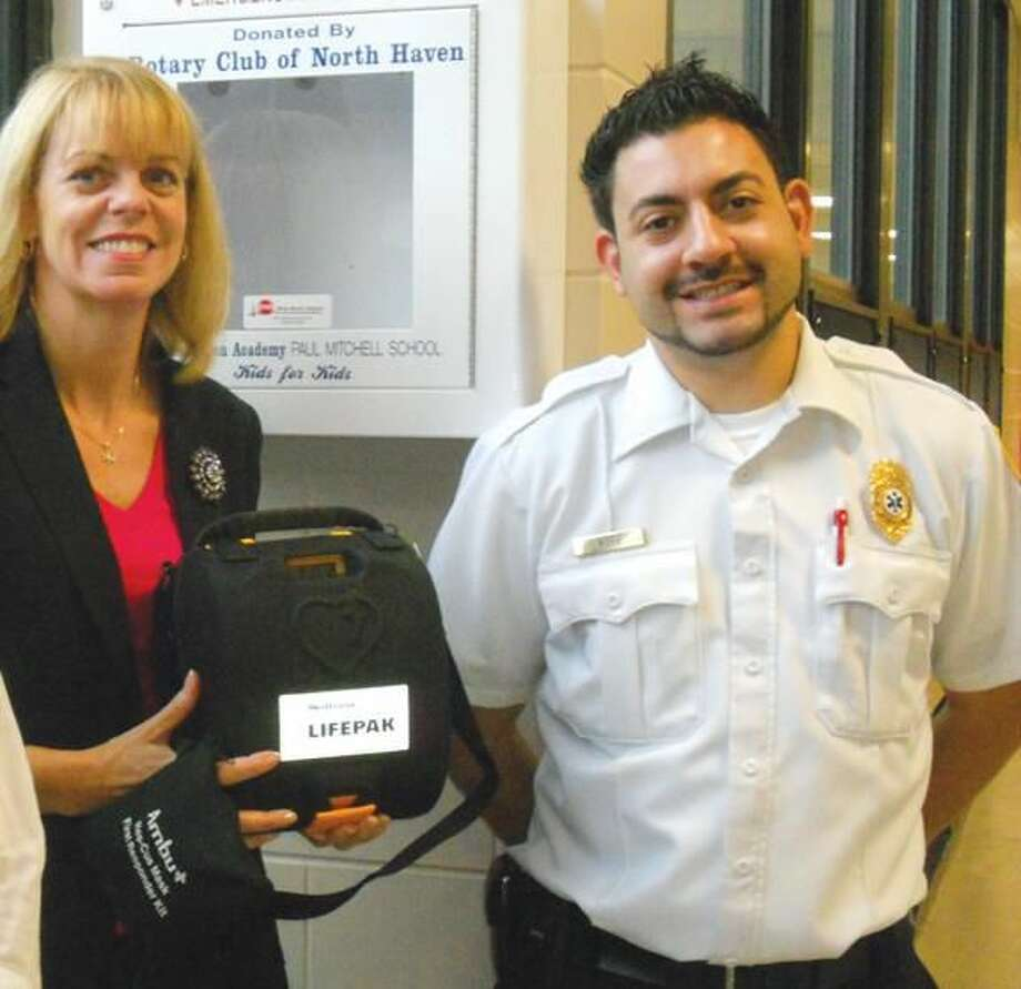 Clintonville Elementary School Principal Loretta Dowling and Mark Lesage posed with an AED obtained through the North Haven Rotary Club.