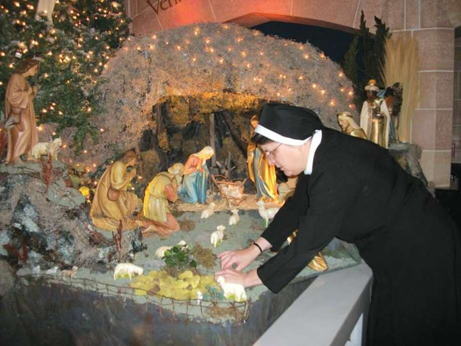 Photo by Lynn Fredricksen Sr. Mariette Moan puts the finishing touches on a Presepio she created in the Chapel at Sacred Heart Academy. The elaborate scene will be on display through the Christmas season.