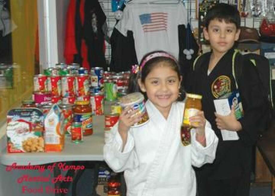 Submitted Photo Ricardo and Areli Jiminez donating food to help the less fortunate.