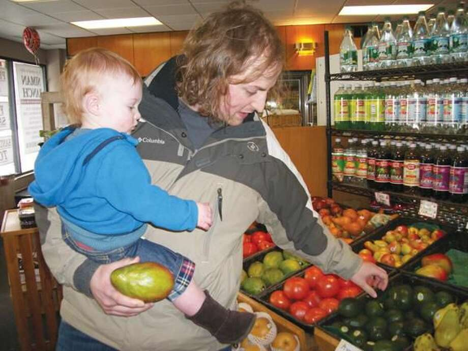 Photo by Lynn Fredricksen Jarrod Ratcliffe, of Hamden, is starting his son, Finlay, 14 months, out early when it comes to learning to select fresh produce. The father and son were shopping for dinner recently at Whitneyville Food Center. Ratcliffe, who recently relocated to the neighborhood, said his wife is a Hamden native who often shopped at the store when she was growing up.