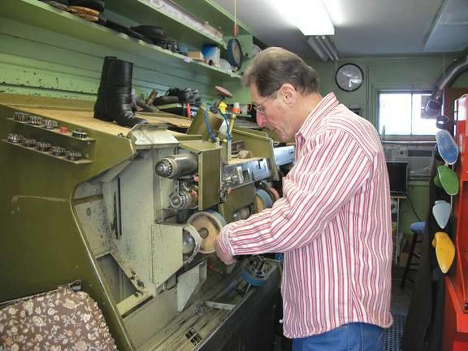 Photo by Lynn Fredricksen Ed Caso demonstrates one of the machines he uses in his shoe repair business. He has owned and operated North Haven Shoe Repair on Linsley Street for 46 years.