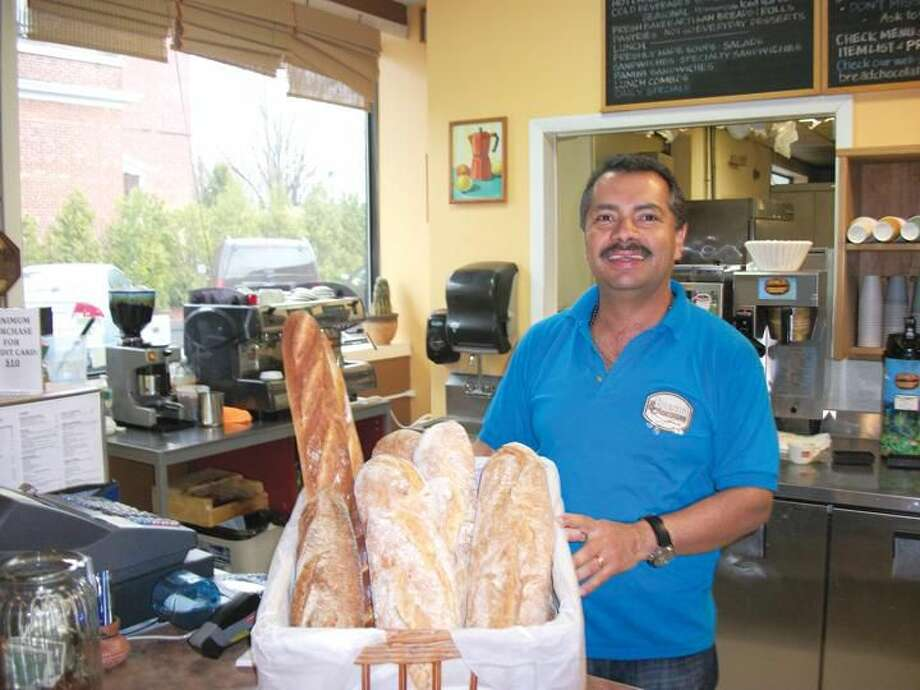 Photo by Lynn Fredricksen Jaime Zapata, who owns Bread and Chocolate at 2457 Whitney Avenue in Hamden, shows off some of the artisan breads he offers for sale. Bread and Chocolate offers breakfast and lunch items as well as a variety of breads and desserts.