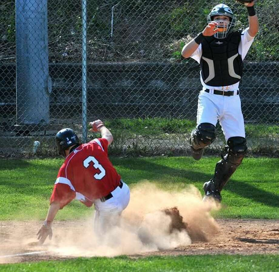 Cheshire's Kevin Mirando slides into home for a run as Hamden catcher Christian Colon jumps for the late throw. Photo-Peter Casolino/Register pcasolino@newhavenregister.com