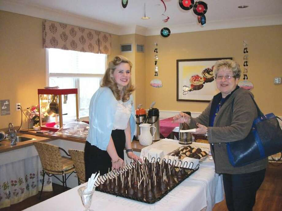 Photo By Lynn Fredricksen Dressed in a vintage 1950s outfit, Kate Taylor, a server at Maple Woods, serves up a chocolate covered strawberry on a stick to Josephine Marra. The two were at a fundraising event to benefit the Hamden Senior Wish Society held recently at Maple Woods.