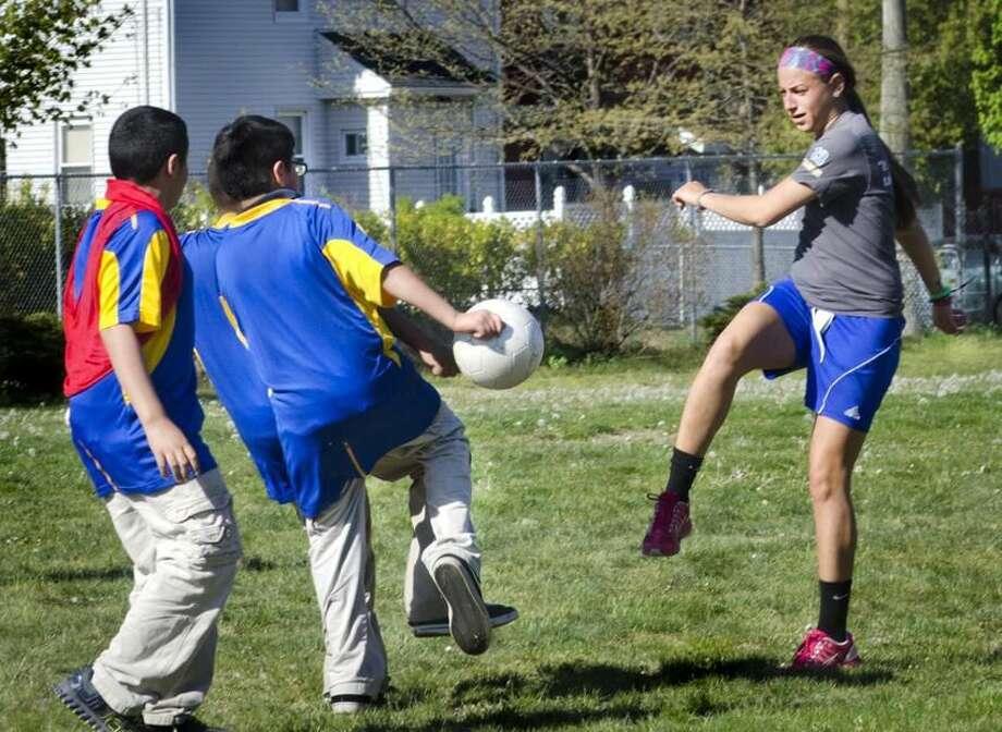 New Haven-UNH soccer player, Alyssa Zargos (R), tries to kick past Diego Padilla Padilla (C),10, as they practice at John Daniels School. Melanie Stengel/Register