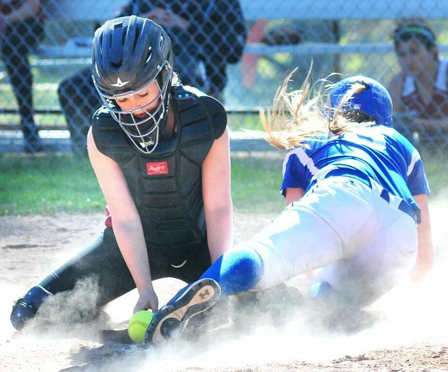 Kristen Domek of West Haven is safe at home as Sacred Heart catcher Angela Onofrio (lerft) traps the ball on the ground in the third inning in Hamden on 5/1/2013.Photo by Arnold Gold/New Haven Register