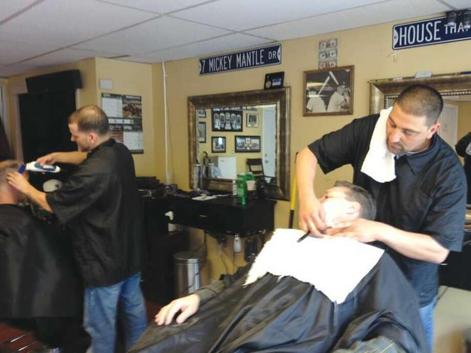 """Photo by Lynn Fredricksen Rob Palmieri gives his friend, Michael Nazario, of North Haven, one of his specialty """"Cut Throat Shaves"""" at Palmieri's shop, Figoro's Barber Shop at 3820 Whitney Ave. in Hamden. In the background, barber Brandon Nalle, gives Joe Chauncy a trim."""