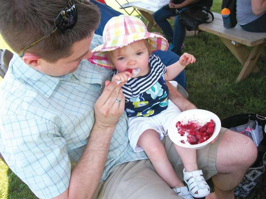 Photo by Lynn Fredricksen Lucy Wright, 1, enjoys her first Strawberry Festival at Hindinger Farm last week. Young Lucy attended the event with her father, Kyle, mom Emily and four-year-old sister, Samatha. The family, from Hamden, came to enjoy some wholesome fun as well as plenty of strawberries.