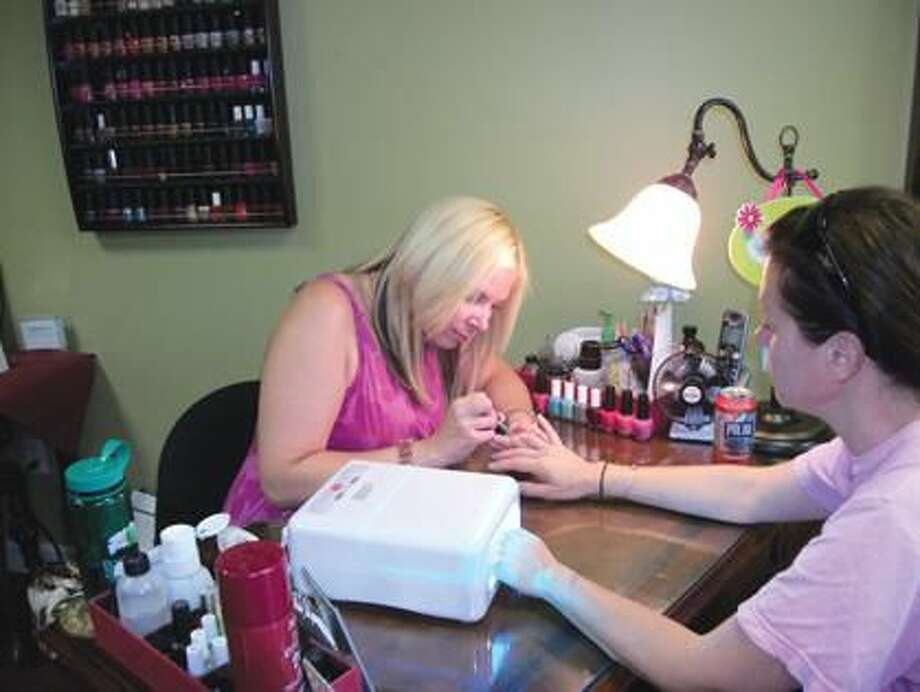 Photo by Lynn Fredricksen Kris Bessette loves her job creating art work on her clients' nails. Here, she applies a shellac manicure for Laura Crouch, of North Haven.
