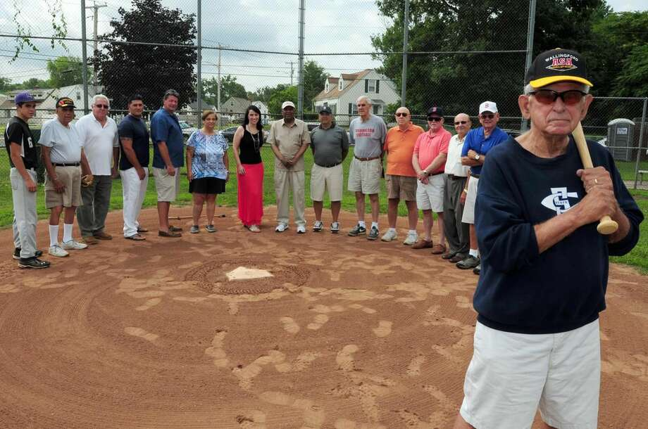 Peter Hvizdak — Register Former Hamden Mayor John Carusone, 77, far right, is putting together a group of athletes for an old timer's game at Hamden's Rotchford Field. From left rear: Spencer Bryden of North Branford, 15; Mike Johnson of Hamden, 87; Dave Rosadini of North Haven, 64; Mike O'Keefe of Hamden, 35; Dennis O'Keefe of Hamden, 65; Rose Mentone of Hamden; Laura Gervais of the March of Dimes; Sam Burrell of Hamden, 80; Gene Zurolo of Cheshire, 68; Bob Stefanowski of North Haven, 83; Vin Virgulto of Hamden, 72; George Hanchette of Northford, 74; Vincent J. DiLauro of New Haven, 71; and Ed Lewis of Milford, 77. at Rotchford Field in Hamden Wednesday July 24, 2013.