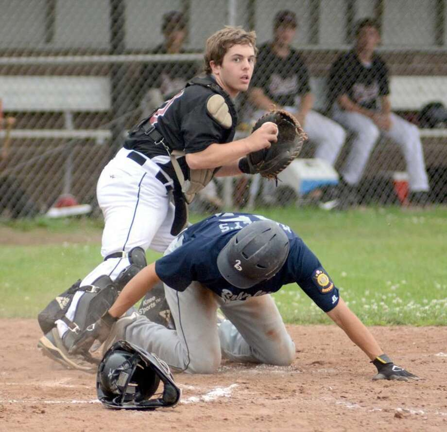 Photo by Dave Phillips North Haven catcher Ryan Harger looks to throw to first base after getting Chris Stankiewicz out at the plate during Post 76's 5-1 loss to Branford on Sunday.