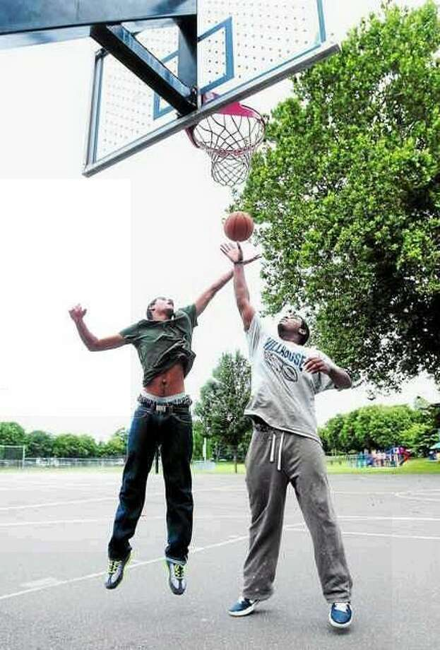 Jalil Austin (left), 16, of Chicago and Khalid Fleming (right), 20, of New Haven play basketball at Goffe Street Park in New Haven on 7/26/2013. (Arnold Gold/Register)