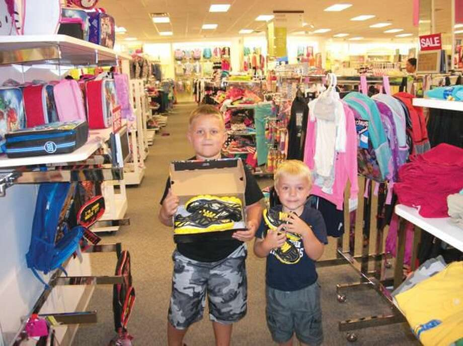 Photo by Lynn Fredricksen Dyllon Currier, 7, and his brother Jake Currier, 4, both of Hamden, shopped with their mother and grandmother for back to school clothes at Kohl's in Hamden as part of tax-free week. Here, they show off their new sneakers, which Jake says will help him run faster.