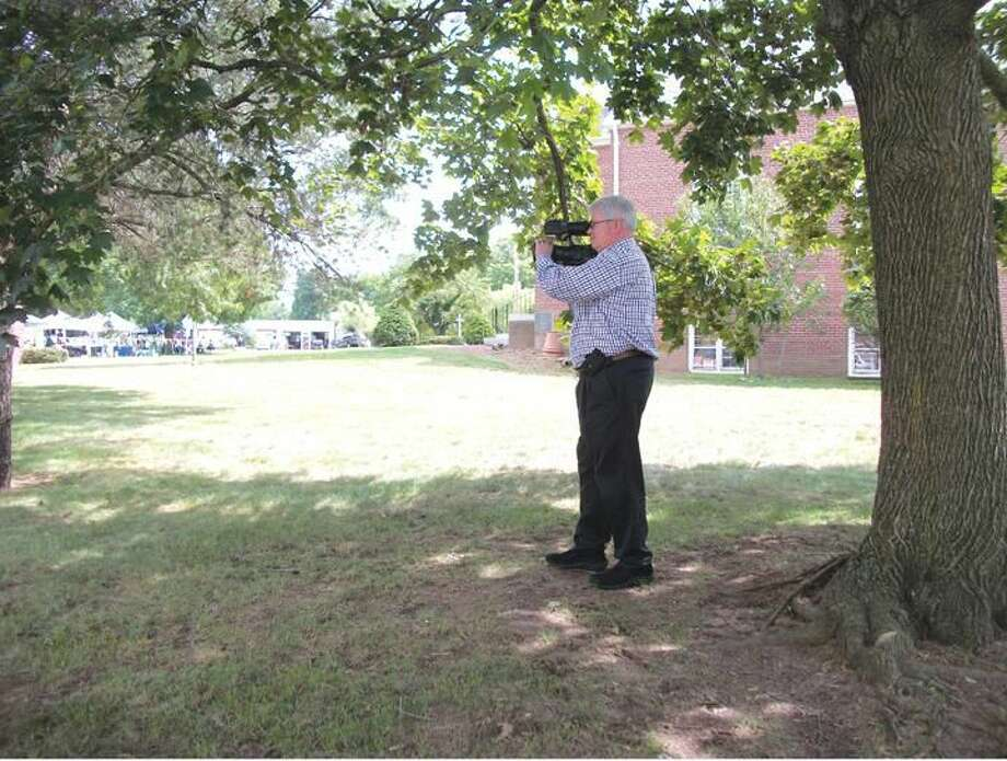 Photo by Lynn Fredricksen Kevin Rossi, of Timeless Moments Video, Inc., shoots some video of the Festival of Angels on the North Haven Green last week. Rossi, who owns the business with his wife, LaVala Rossi, enjoys his work and being a part of people's special events.