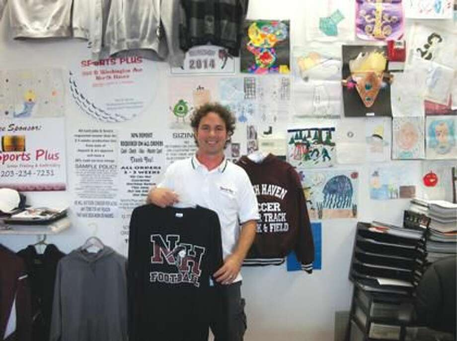 Photo by Lynn Fredricksen Bob Chancio, who owns and operates Sports Plus at 369b Washington Avenue, shows some of his wares. His business provides screen printing and embroidery services. Behind him he displays a large collection of his children's artwork.
