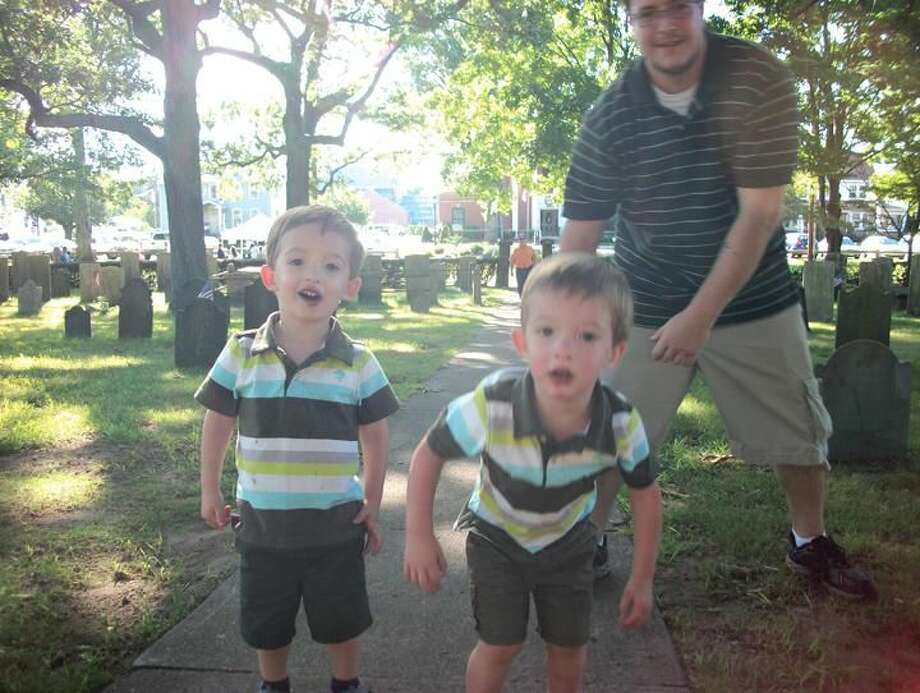 Photo by Lynn Fredricksen Twin brothers Miles and Max, 2, explored every inch of the Town Green on Saturday when their parents took them to the Italian Festival of Angels. Here Dad Eric runs them down in the Ancient Cemetery.