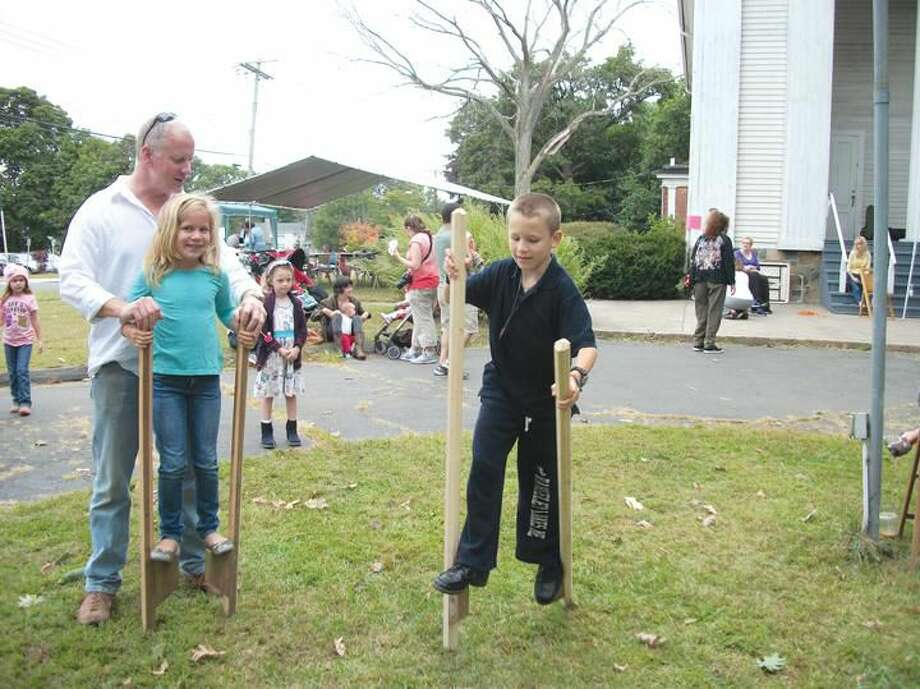 Photo by Lynn Fredricksen Joe Callaghan helps his daughter, Dani, 8, as she and her brother, Isaac, 11, give stilt walking a try at the third annual Whitneyville Fall Festival recently. The event brought 50 vendors, artists and musicians out for a fun-filled day.