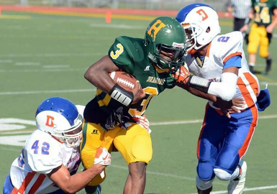 Photo by Dave Phillips Hamden's Maliek Wiliamson carries the ball as Danbury's Elijah Duffy (2) and Eric Henry (42) try to take him down during the Green Dragons' 26-10 victory Friday afternoon at Hamden High.