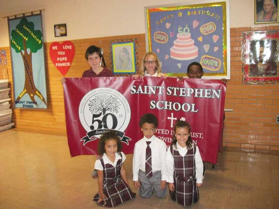 Photo by Lynn Fredricksen Students at St. Stephen's School are thrilled to be celebrating its 50th Anniversary. Pictured standing, from left, are Sean Cox, Emma Acampora and Seamus Mfarinya. Kneeling in front of banner are kindergarteners Alana Mutts, Sean Figueroa and Maria Testa, granddaughter of school principal Maria Testa.
