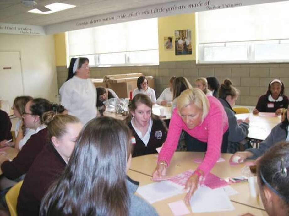 Photo by Lynn Fredricksen Kim Dwyer (in pink sweater) leads a group of girls at Sacred Heart Academy as they make pink beaded bracelets and buttons with inspirational messages to encourage cancer patients who are undergoing chemotherapy. All last week SHA students participated in a variety of activities to raise awareness and to honor those who have or have had cancer.