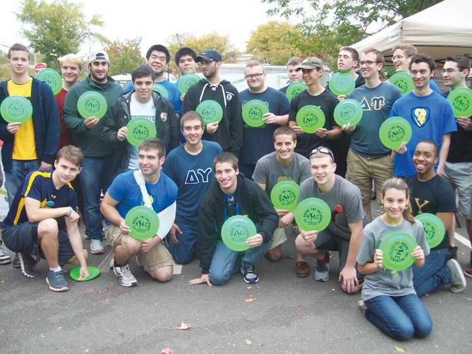 """Submitted Photo Members of Quinnipiac University's Delta Upsilon Fraternity at Hamden's recent Multicultural Festival, joined HYAC's """"Positive Choices"""" Committee to convey the message, """"Fly Above the Influence."""" Delta Upsilon members, along with Committee members, gave frisbees imprinted with that important message to younger attendees at the event."""