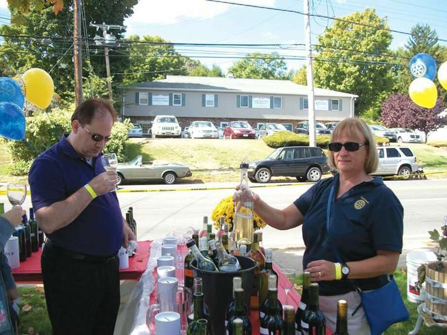 Photo by Lynn Fredricksen Rotarian Bernadette Casella pours some wine for Sid Mautte, 3rd, at the Rotary-sponsored 12th Annual Day of Wine and Roses held at Forget Me Not Florist, 39 State Street. Several hundred people attended the event to benefit the local Rotary club's scholarship fund.