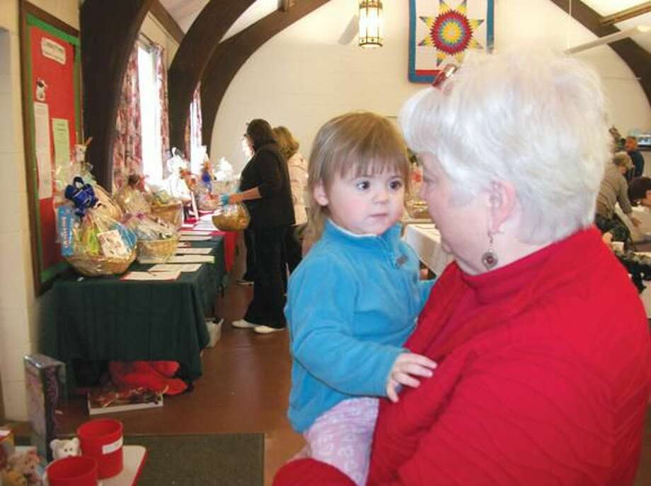 Photo by Lynn Fredricksen Little Sophia Palmisano shares a moment and a hug with Jane Davis at the annual Harvest Fair at St. John's Episcopal Church on Saturday. Sophia is a third-generation member of the parish, where Davis serves as administrator.