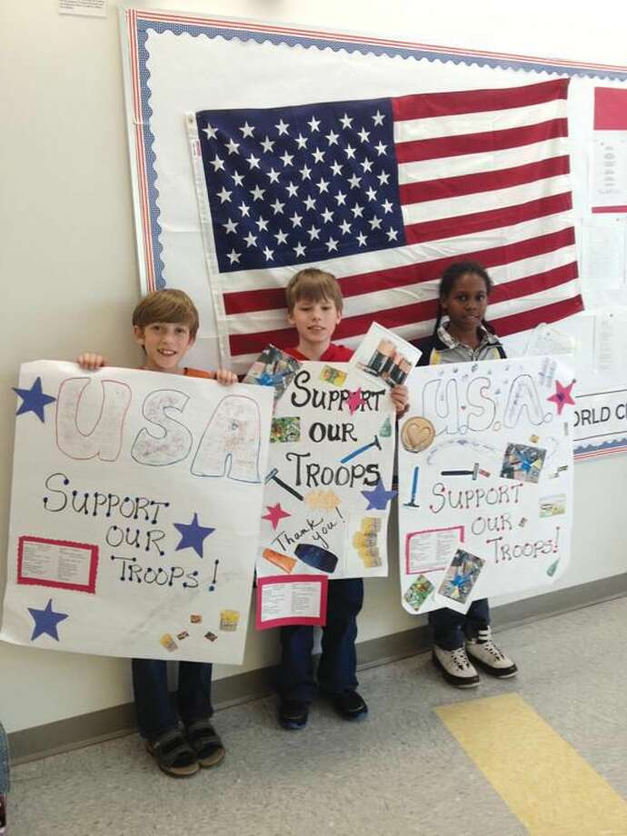 Submitted Photo Hamden Middle School students, left to right: Carter Richards, Mark Esposito, and Jelin Hinto, display their posters in support troops deployed in Afghanistan.