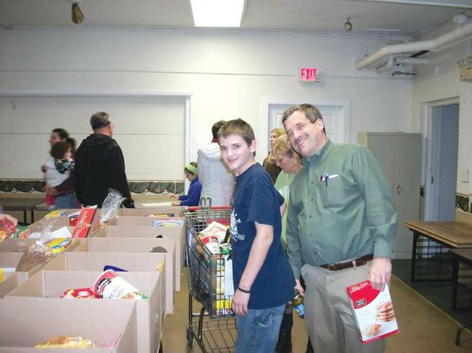 Photo by Lynn Fredricksen The Rev. Scott Morrow clowns around with parishioner Andy Romaniuk as the two work to fill boxes for the Food Bank's annual Thanksgiving food distribution. Housed in the Congregational Church, the food bank provided for 90 needy families this Thanksgiving.