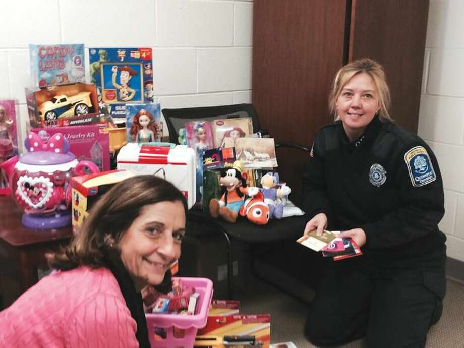 Submitted Photo Patricia Polvani (left), a secretary in the Department of Public Safety at Quinnipiac University, and Shanon Grasso, a public safety officer, have helped organize a 'Ticket for a Toy' drive to benefit Hamden children. Those who donate a toy, gift certificate, gift card or movie pass with a value of at least $10 will have one unpaid parking ticket expunged from their record at Quinnipiac.