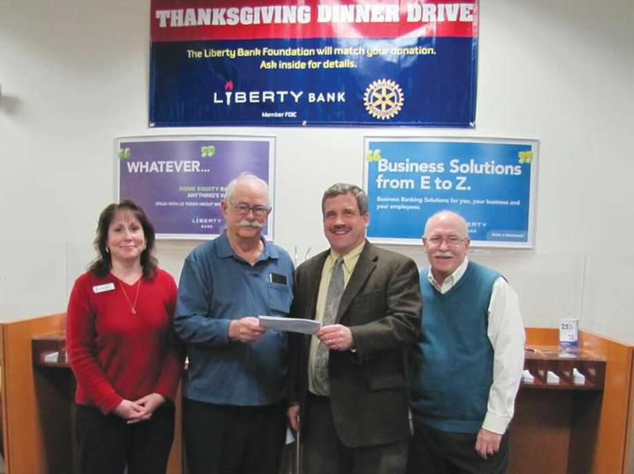 Submitted photo by David Marchesseault, Rotary Publicity Chair North Haven Liberty Bank's Interim Manager Kimberly Pierce and Rotarian John Henry Graef Jr. present a $6,421.46 check to Rev. Scott G. Morrow as 2013 Rotary Food Drive Chairman Bill Espowood looks on.