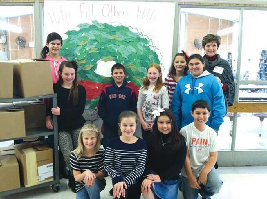 Submitted Photo Students of Leadership Council are pictured with Geraldine Woods Connecticut Chapter Co-President of the Pajama Program with the items collected in front of a wreath that represents each book and pajama received.""