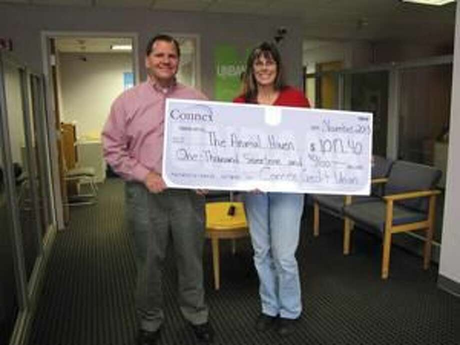 Submitted Photo Carl Casper, Connex VP of Customer Advocacy, left, presents a check to Kate Cryder, Animal Haven Manager.