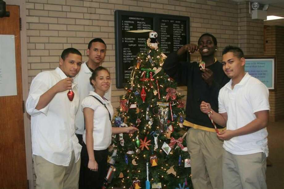 """Submitted Photo Manny Almodovar, John Irizarry, Juanita Hutchings, Catavius McClain, and Brian Gonzalez — students of Eli Whitney Technical High School — hang Christmas ornaments on a tree donated to the annual Trees of Hope fundraiser that benefits the Ronald McDonald House of New Haven. The name of the tree was """"The Twelve Trades of Christmas."""""""